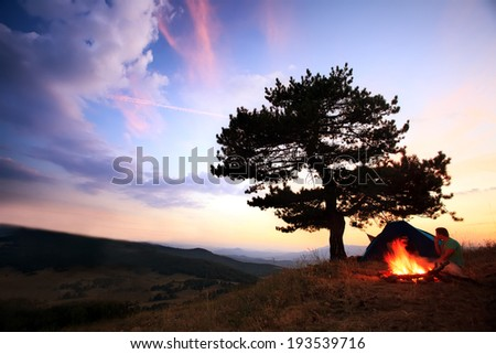 Blazing bonfire in mountain, scenic HDR camp background with two man  - stock photo