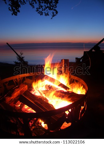 Blazing campfire at sunset along the beautiful beach of Lake Superior in northern Michigan