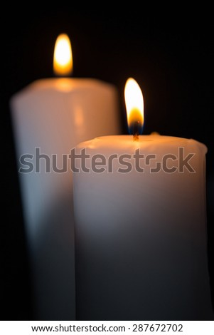 Blazing candles on black background