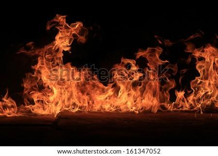 Blazing flames over black background - stock photo