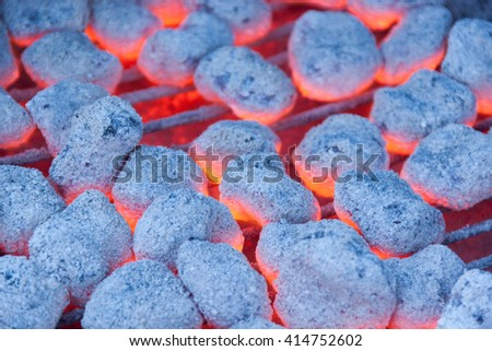 Blazing hot charcoal burns over iron grates - stock photo