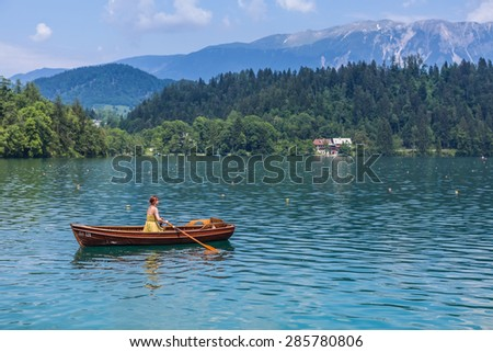BLED, SLOVENIA - JUNE 3, 2015: Single female steering the wooden boat in lake Bled. Bled is a glacial lake in the Julian Alps in northwestern Slovenia.