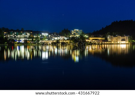 BLED, SLOVENIA - 27TH MAY 2016: A view of buildings from across Bled Lake at night. Reflections can be seen in the water.