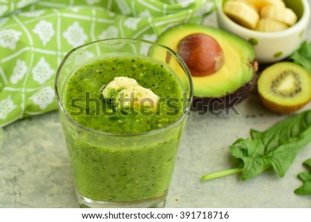 Blended green smoothie with ingredients (banana, kiwi, avocado and spinach)