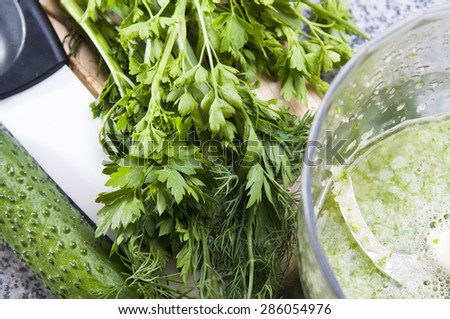 Blender is mixing a green smoothie. Close up of healthy fresh green vegetable smoothie from cucumber, dill and parsley on a marble table, top view - stock photo