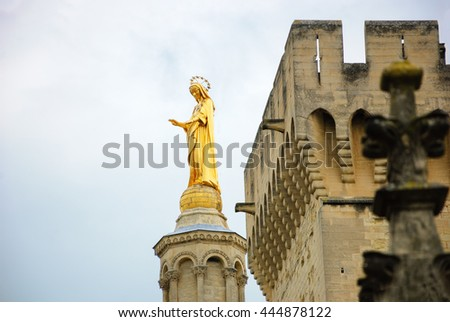 Blessed Virgin Mary. Golden statue of Madonna blessing from the top of Notre Dame Cathedral and the walls of Papal palace in Avignon (France)  - stock photo