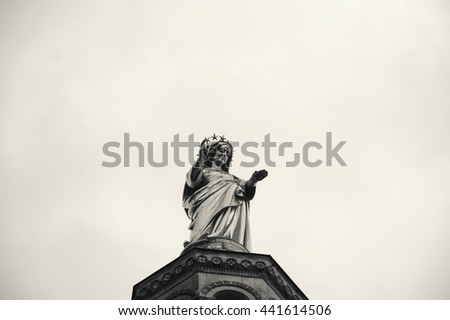 Blessed Virgin Mary. Golden statue of Madonna looking from the top of Notre Dame Cathedral. Avignon (France) Black and white photo. - stock photo