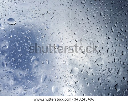 bleu sky behind rain drops on a window