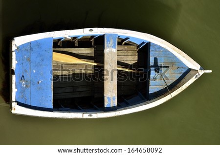 Bleu small boat seen from above with a paddle - stock photo
