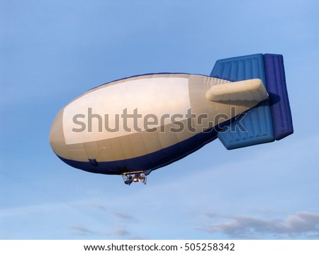 Blimp with a pilot on the background of blue sky.