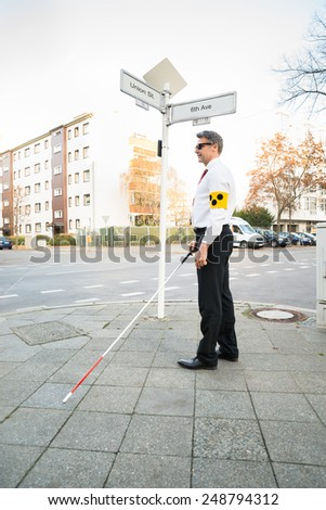 Blind Man Wearing Armband Crossing Road Holding Stick - stock photo