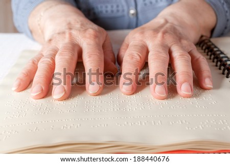 Blind old woman reading text in braille language - stock photo
