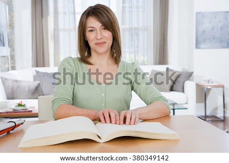 Blind woman reading braille - stock photo
