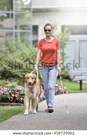 Blind woman walking in park with dog assitance - stock photo