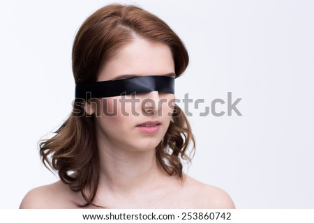 Blindfold beautiful woman over gray background - stock photo
