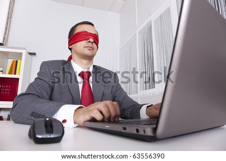 Blindfold businessman at the office working with his laptop - stock photo