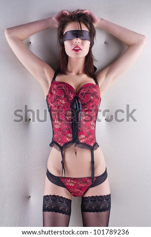 Blindfold seductive woman in a corset and stockings standing in front of white wall - stock photo