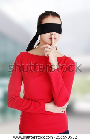 Blindfold woman with finger on lips - stock photo