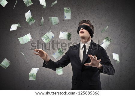Blindfolded businessman trying to catch a hundred-euro banknotes flying in the air - stock photo
