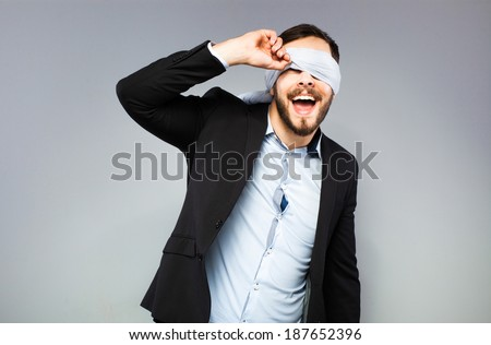 blindfolded man trying to see something - stock photo