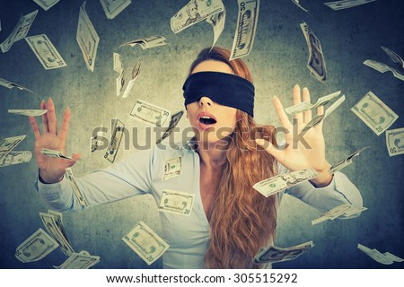 Blindfolded young entrepreneur businesswoman trying to catch dollar bills banknotes flying in the air on gray wall background. Financial corporate success or crisis challenge concept   - stock photo