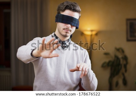 Blindfolded young man at home in living room cannot see, trying to find his way with his hands - stock photo
