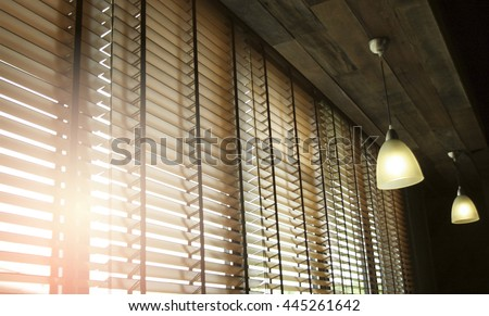 Blinds in a home catching the sunlight with burst light - stock photo
