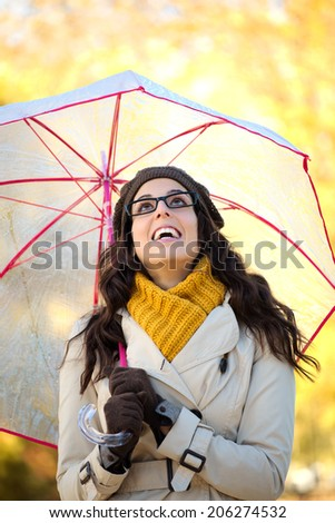 Blissful woman with glasses holding umbrella under the rain in a cold autumn day. Fashion brunette laughing and looking up. - stock photo