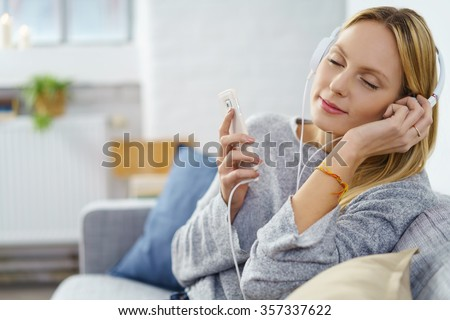 Blissful young woman sitting listening to music on her mobile phone on stereo headphones at home as she relaxes with closed eyes on a sofa - stock photo