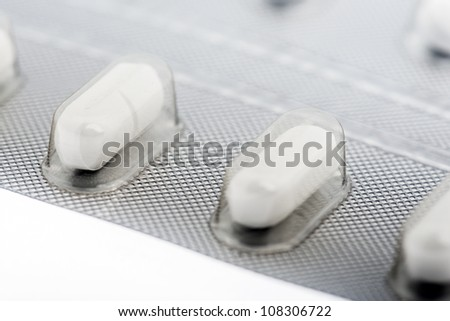Blister pack of pill on white background, closeup - stock photo