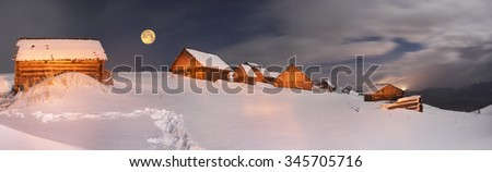 Blizzard covered alpine fields shepherds in the Ukrainian Carpathians. Beautifully lit golden light barns and houses shepherds - cold winter and frost on the background of mountain peaks - stock photo
