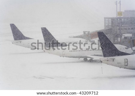 Blizzard on an international airport, airplanes waiting in the snow, free copy space - stock photo