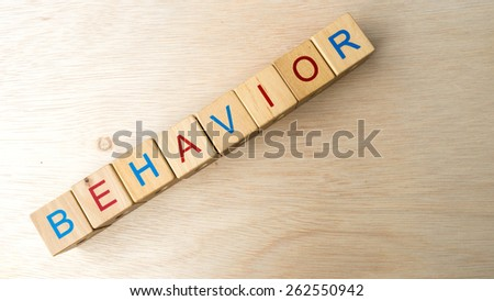 Block of alphabet letters forming the word BEHAVIOR on wooden surface. Concept of common marketing business terms. Slightly defocused and close-up shot. Copy space.