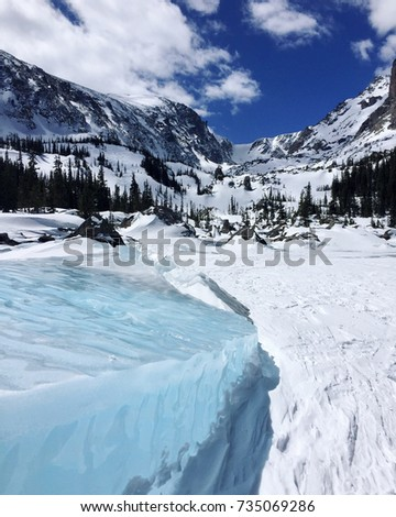 Block of bright blue ice on a frozen lake with snowy mountains and blue sky in the background