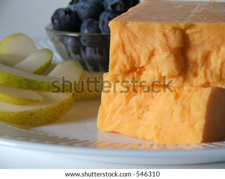 Block of cheese in foreground, with fresh fruits in the background. - stock photo