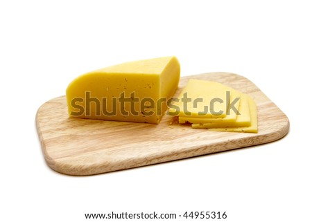 block of cheese with cut pieces on cutting board, isolated on white background