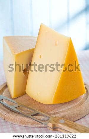 block of edam cheese on kitchen table - stock photo