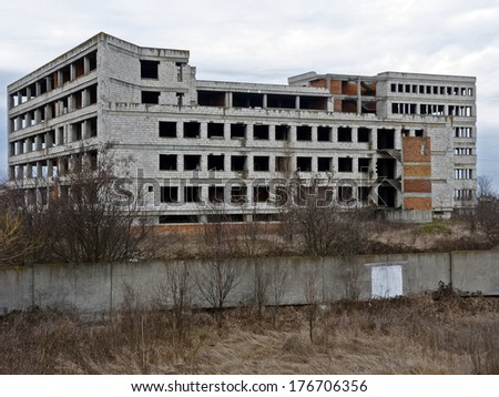 Block of flats under construction. Brick and cement textures, trees and bushes around it - stock photo