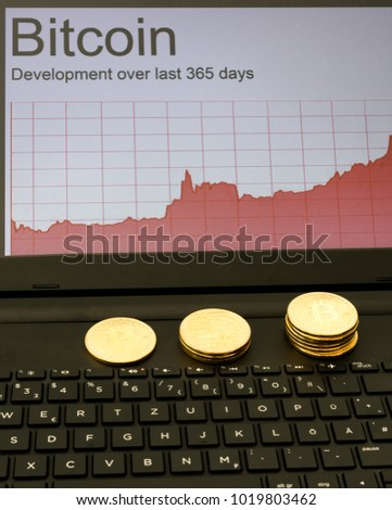 Blockchain concept : Rise of Bitcoin price. Laptop computer screen showing increasing price graph with coins of the cryptocurrency.