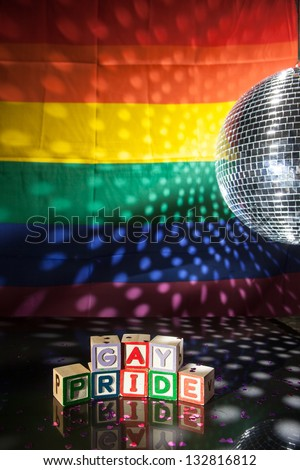 Blocks spelling out gay pride under light of disco ball with rainbow flag - stock photo