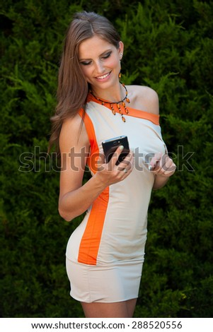 Blog style beautiful brunette woman in fashionable dress posing in park presenting garment