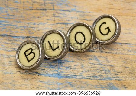 blog word spelt in vintage typewriter keys against grunge wood - stock photo