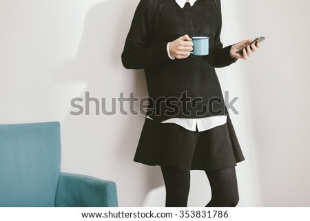 blogger girl checking her smartphone while drinking a coffee - stock photo