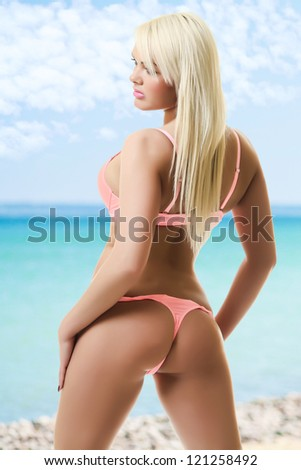 blond and attractive woman in pink bikini - stock photo