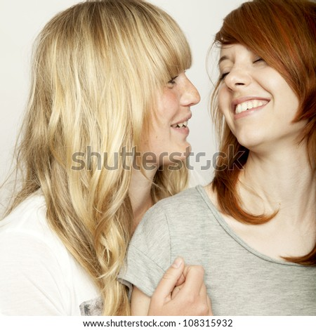 blond and red haired girls are laughing and have fun - stock photo