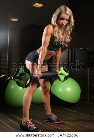 Blond athletic fitness woman holds barbell and posing in a gym.