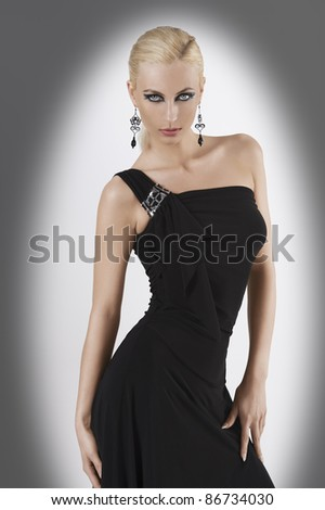 blond attractive young woaman in black dress and black earring looking in camera with strong and sexy eyes and wit sexy pose looking towards the camera - stock photo