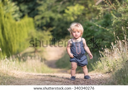 Blond baby girl in blue jeans costume walking forward or standing on green path in a garden or forest, baby's first steps - stock photo
