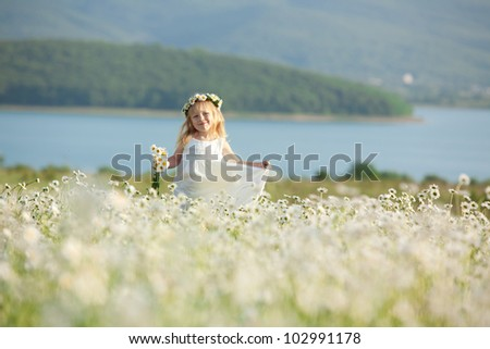 Blond baby girl in wreath in field of chamomiles