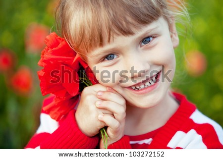 Blond baby girl with bouquet of poppies outdoor